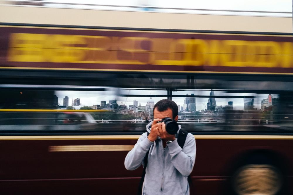 Photographer taking a picture in London while a moving bus is passing and the cityscape of London