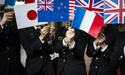 Close up of people in uniform waving small national flags.